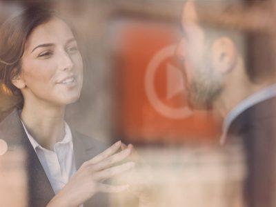 Two people in businesswear talking